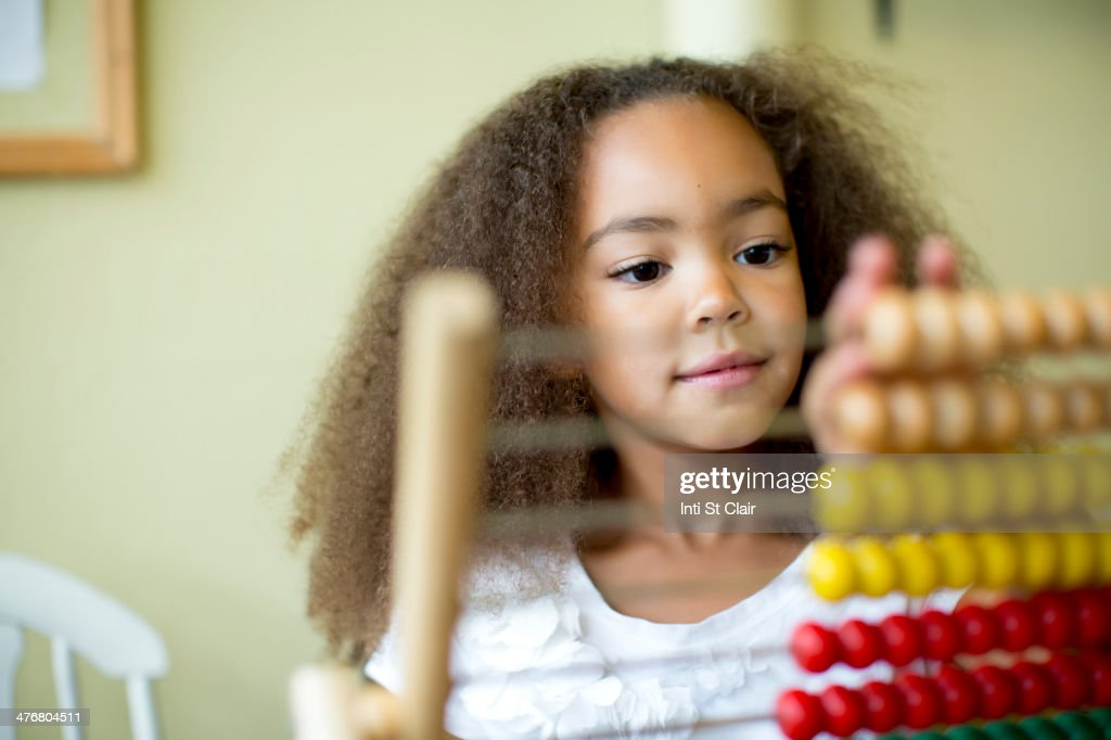 Mixed race girl using abacus