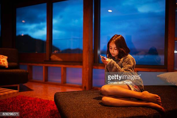 Mixed race girl using cell phone in living room