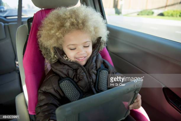 Mixed race girl using digital tablet in back seat of car
