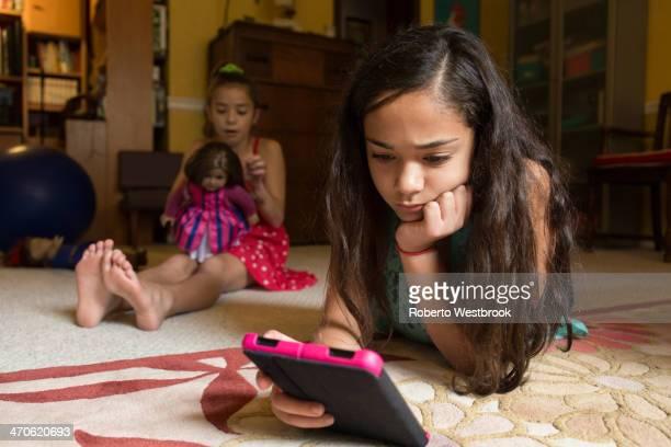 Mixed race girl using digital tablet on floor