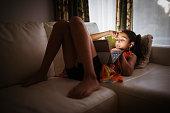 Mixed race girl using digital tablet on sofa