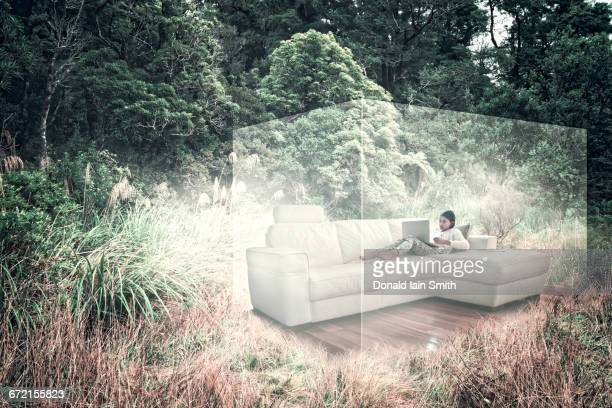 Mixed Race girl using laptop on sofa in virtual cube