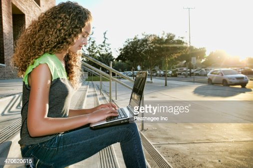 Mixed race girl using laptop on steps : Stock Photo