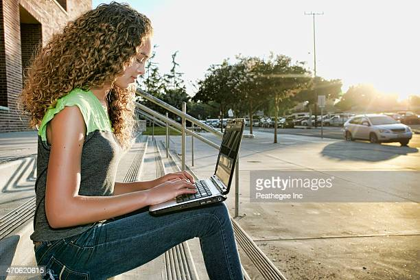 Mixed race girl using laptop on steps