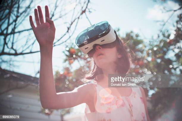 Mixed Race girl using virtual reality goggles outdoors