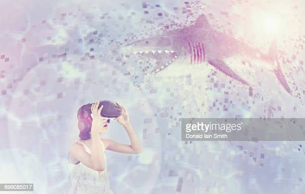 Mixed Race girl using virtual reality goggles watching shark