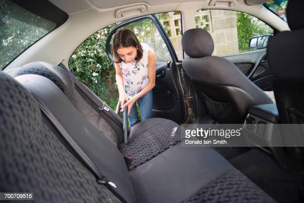 Mixed Race girl vacuuming car interior