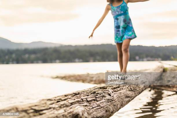 Mixed race girl walking on log