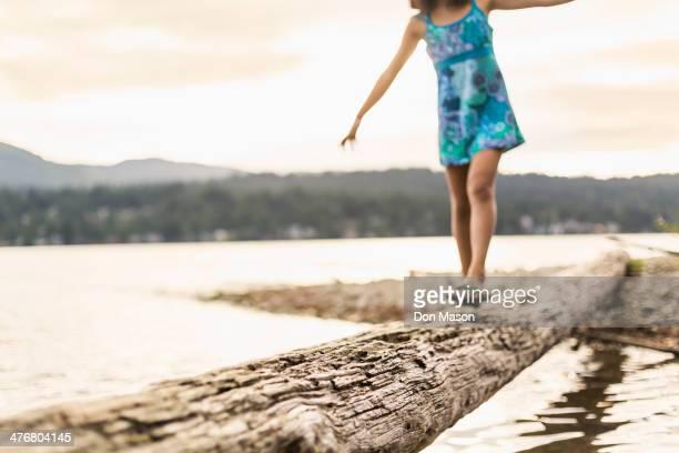 Mixed race girl walking on log
