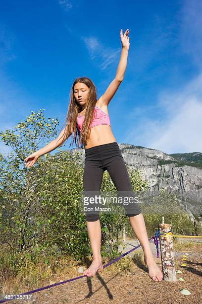 Mixed race girl walking on tightrope