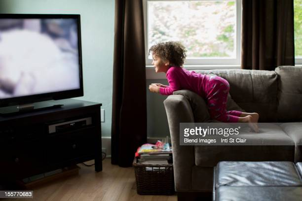 Mixed race girl watching television