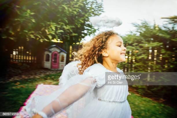 Mixed race girl wearing angel costume in backyard