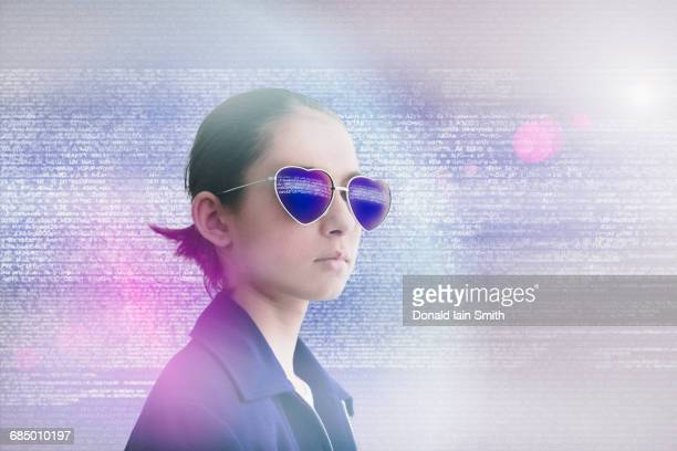 Mixed Race girl wearing heart-shape sunglasses in data cloud
