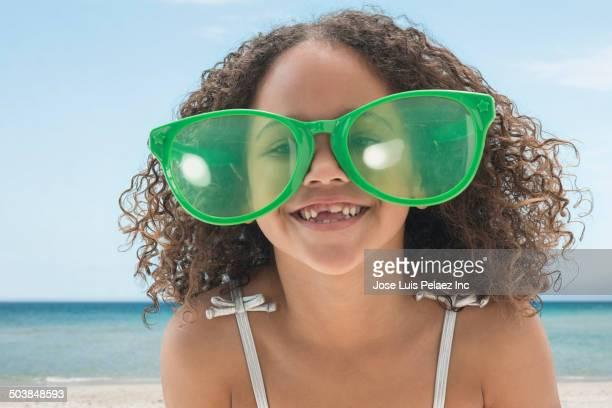 Mixed race girl wearing oversized sunglasses on beach