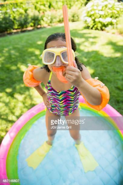 Mixed race girl wearing snorkeling gear in wading pool