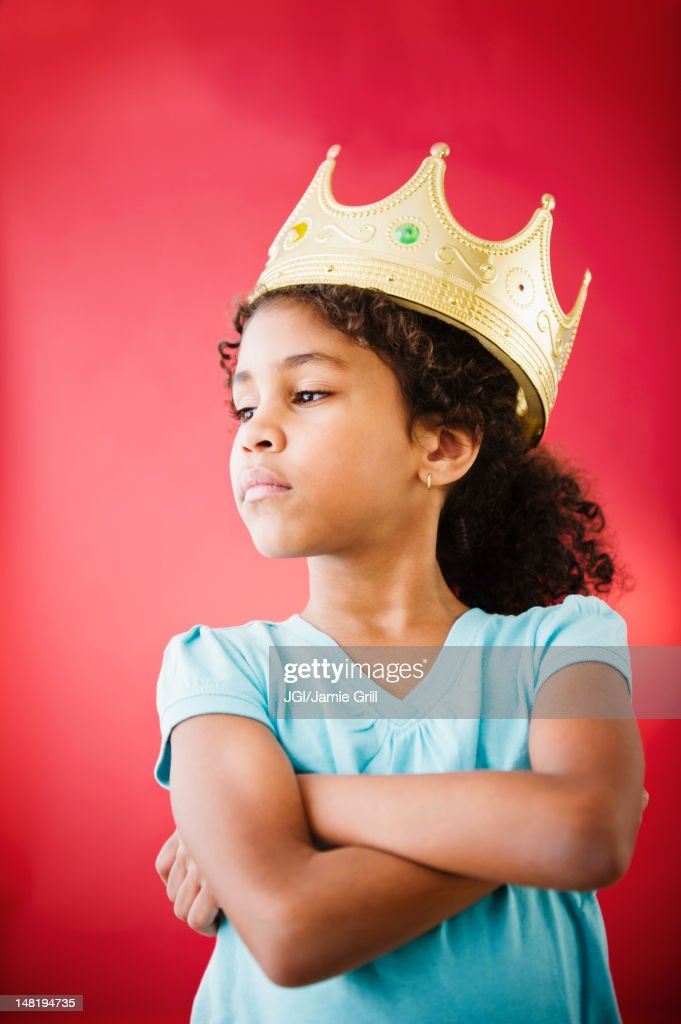 Mixed race girl with arms crossed wearing crown : Stock Photo