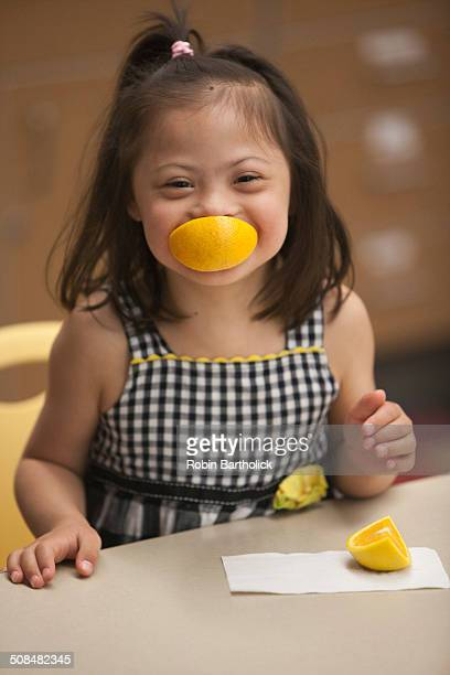 Mixed race girl with Down syndrome eating fruit