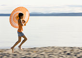Mixed Race girl with parasol at beach