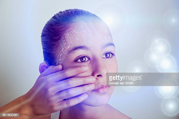 Mixed race girl with technology on her face