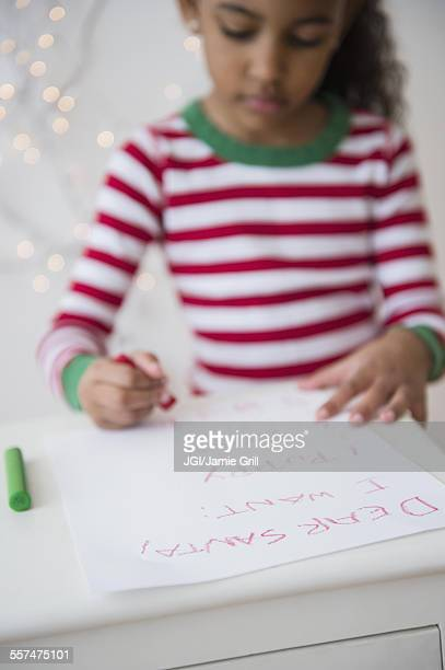 Mixed race girl writing letter to Santa