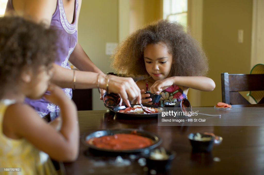 Mixed race girls eating dinner : Stock Photo