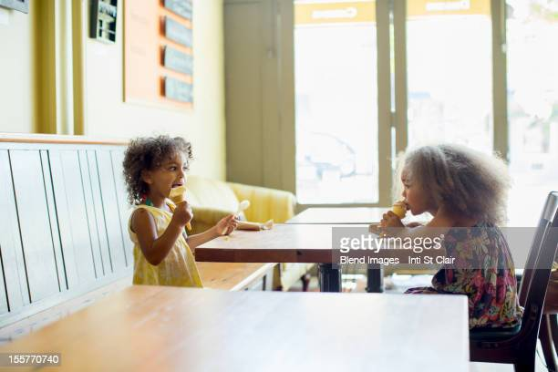 Mixed race girls eating ice cream cones