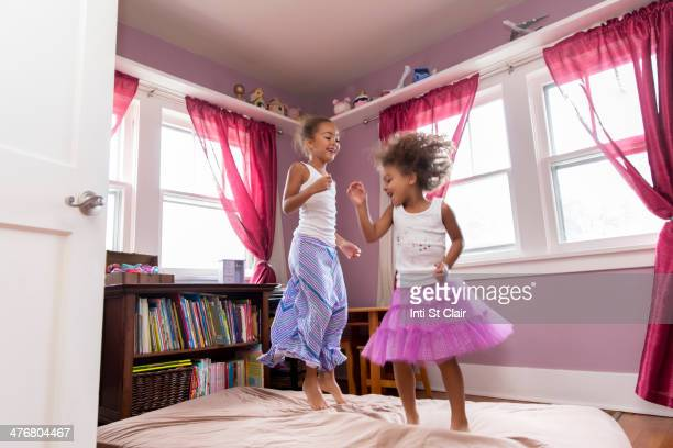 Mixed race girls jumping on bed