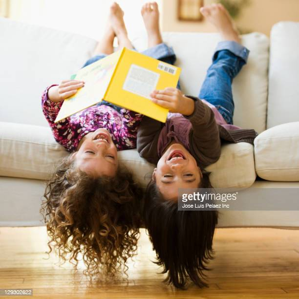 Mixed race girls laying upside-down on sofa reading book