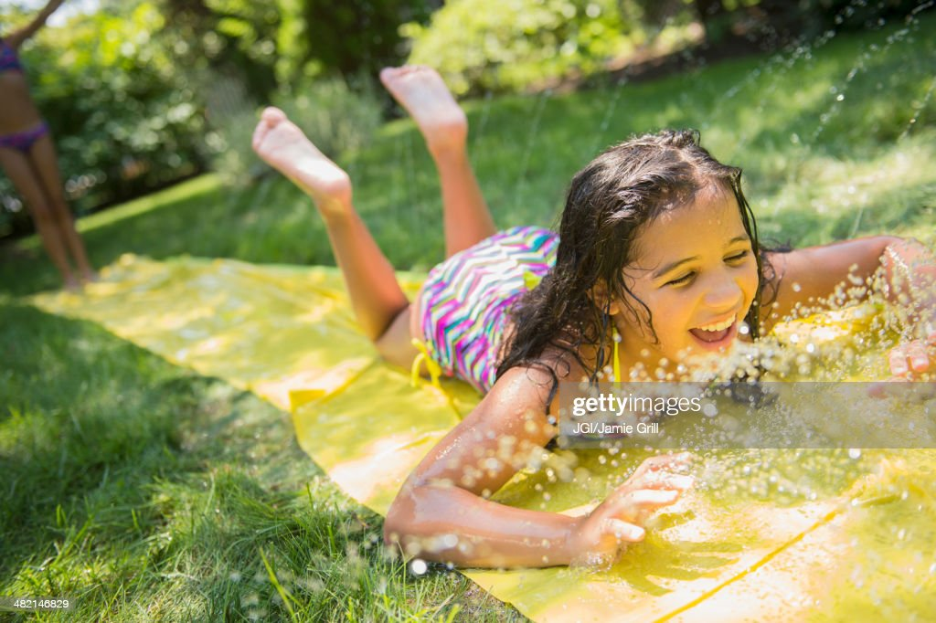 Mixed race girls playing on slip and slide in backyard : Stock Photo
