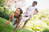 Mixed race girls playing wheelbarrow in backyard