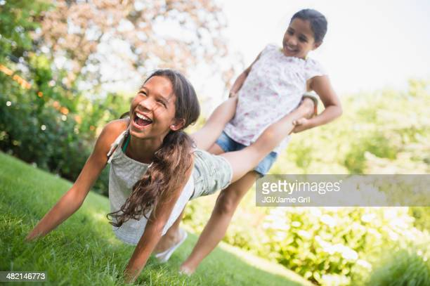 Mixed race girls playing wheelbarrow in backyard