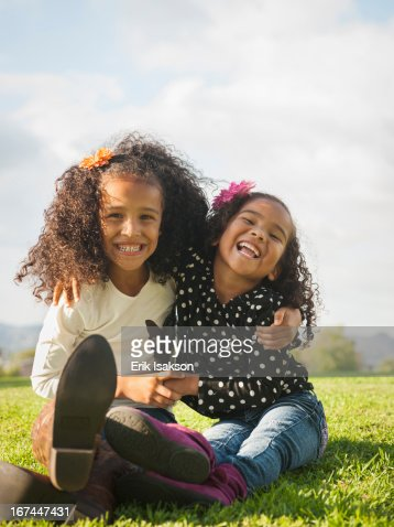 Mixed race girls sitting in grass : Stock Photo