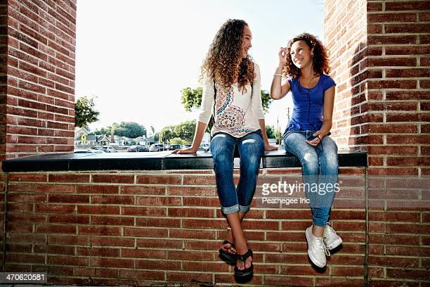 Mixed race girls sitting on brick ledge