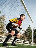 Mixed race goalkeeper protecting goal