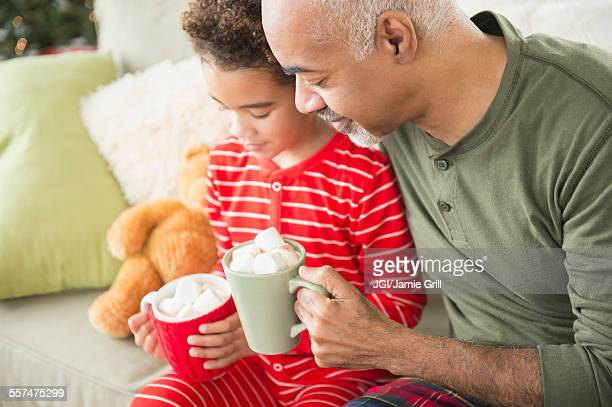 Mixed race grandfather and grandson drinking hot chocolate at Christmas
