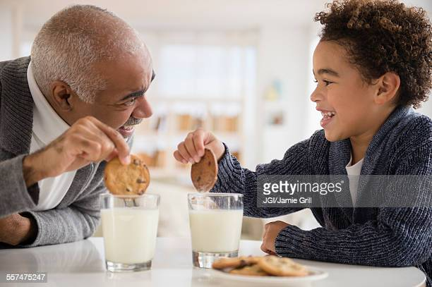 Mixed race grandfather and grandson eating cookies and milk