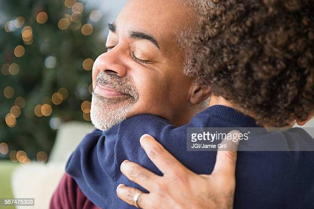 Mixed race grandfather and grandson hugging at Christmas