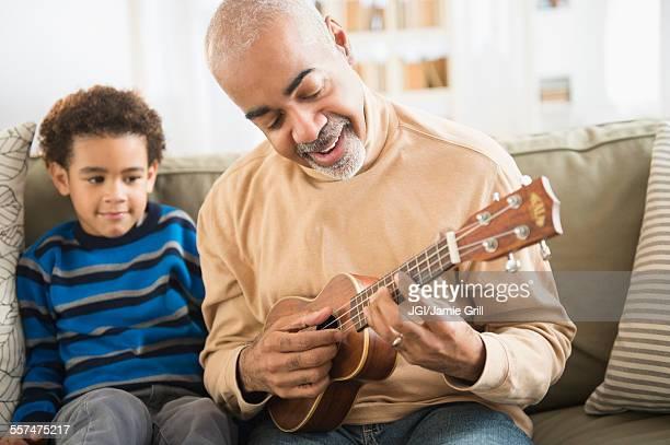 Mixed race grandfather and grandson playing ukulele