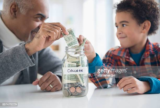 Mixed race grandfather and grandson saving money in college fund jar