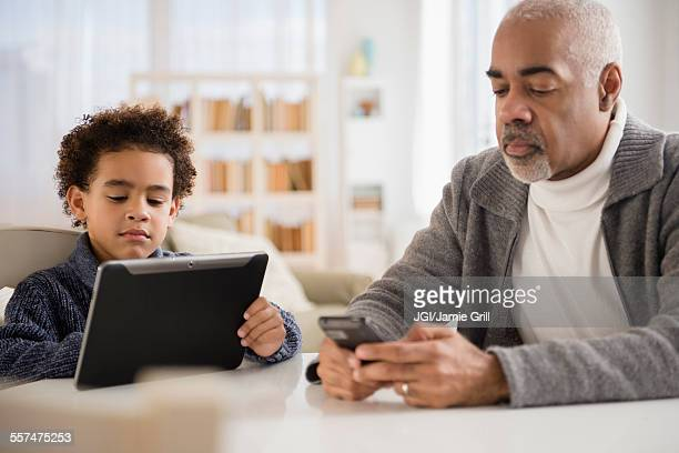 Mixed race grandfather and grandson using cell phone and digital tablet