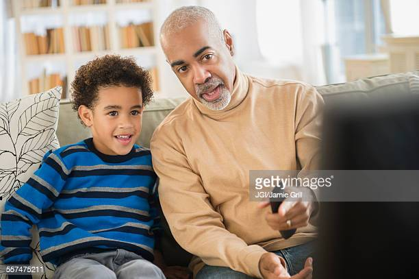 Mixed race grandfather and grandson watching television
