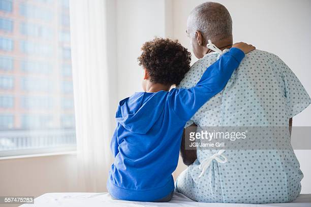 Mixed race grandfather sitting with grandson in hospital