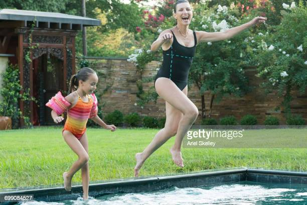 Mixed Race grandmother and granddaughter jumping into swimming pool