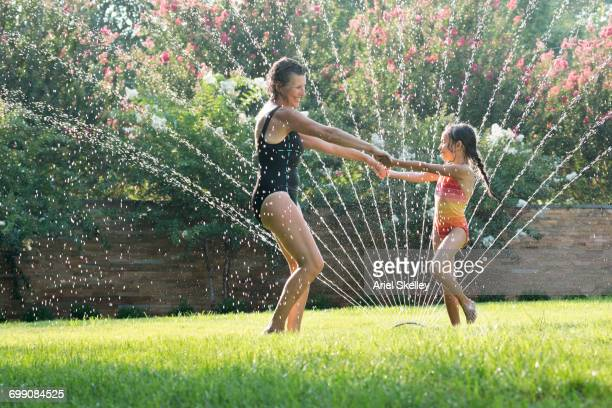 Mixed Race grandmother playing with granddaughter in sprinkler