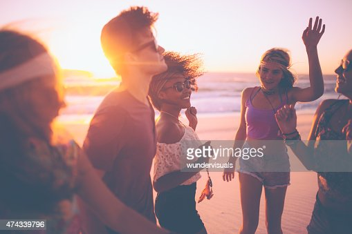 Mixed race group of friends dancing together at a beachparty