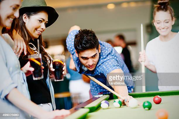 Mixed race group of friends playing pool game in pub