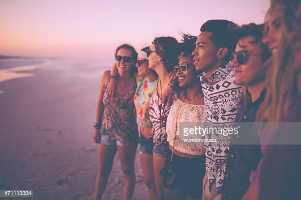 Razza mista gruppo di amici, guardare il tramonto insieme sulla spiaggia