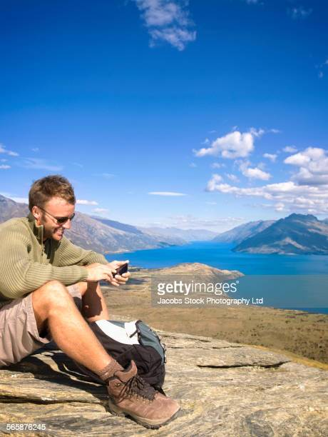 Mixed race hiker sitting on hilltop near lake, Queenstown, South Island, New Zealand