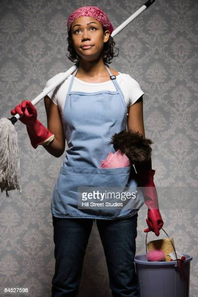 Mixed race housewife standing with cleaning supplies