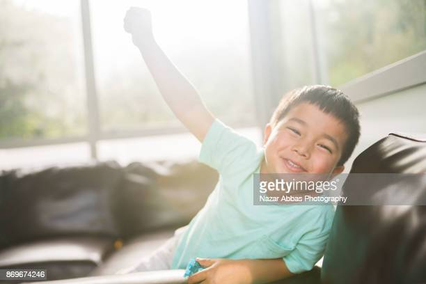 Mixed race kid making a happy face.